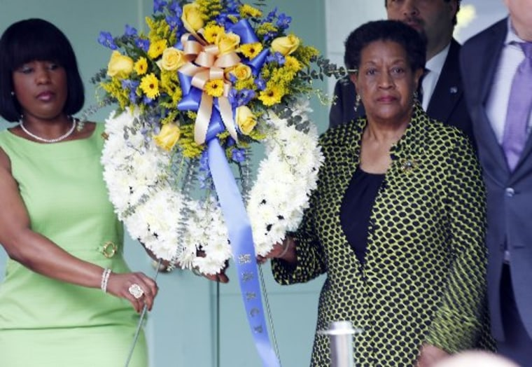 Myrlie Evers-Williams, widow of Medgar Evers, right and Roslyn M. Brock, chairwoman of the NAACP national board of directors, left, carry the wreath to be placed in front of the former home of the slain civil rights leader, Thursday, May 16, 2013, in...