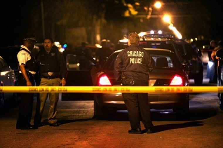 Police investigate the scene where a 15-year-old boy was shot and killed by police after he reportedly pointed a gun at officers during a foot chase on June 17, 2013 in Chicago. (Photo by Scott Olson/Getty Images)