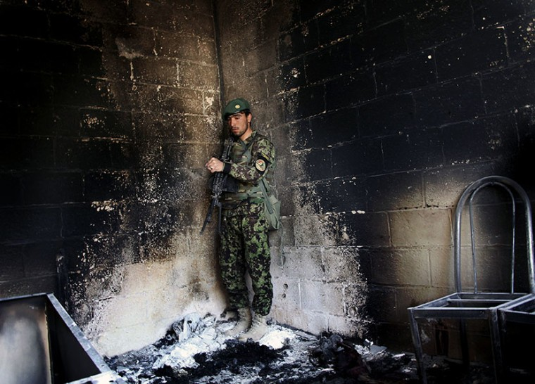An Afghan army soldier stands guard in the destroyed courthouse in Farah, western Afghanistan, Thursday, April 4, 2013. Suicide bombers disguised as Afghan soldiers stormed a courthouse Wednesday in a failed bid to free more than a dozen Taliban...