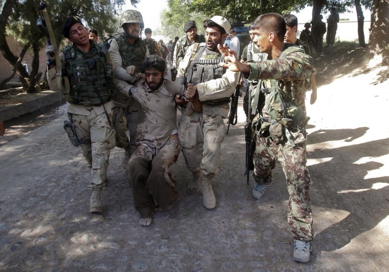 Afghan security forces escort a captured suspected Taliban insurgent during an operation in Sorkhrod district of Jalalabad province, June 19, 2013. (Photo by Parwiz/REUTERS)