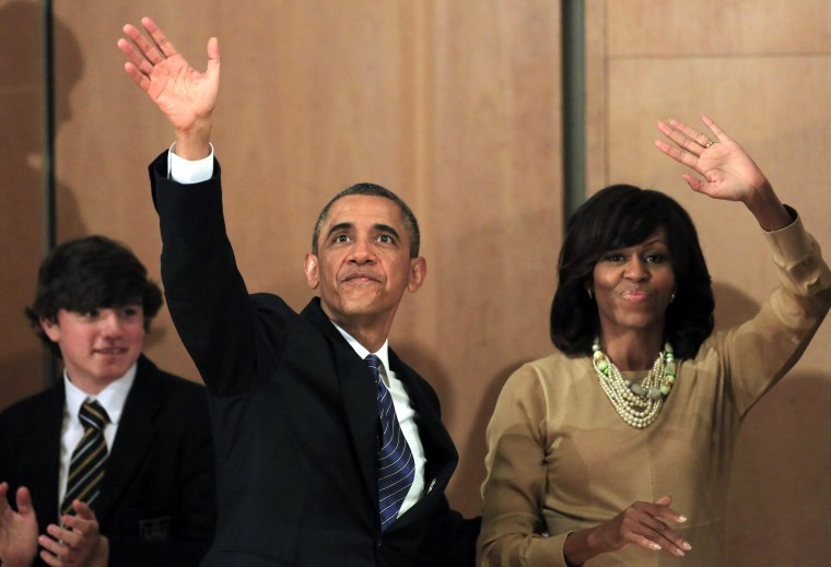 US President Barack Obama, left, waves while walking with First Lady Michelle Obama after he delivered a keynote address ahead of the G-8 summit at Waterfront Hall in Belfast, Northern Ireland on Monday, June 17, 2013. (AP Photo/Peter Morrison)