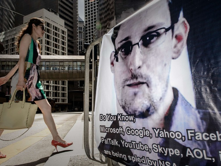 This file picture taken on June 18, 2013 shows a woman walking past a banner displayed in support of former US spy Edward Snowden in Hong Kong.  (Photo by Philippe Lopez/AFP/Getty Images)