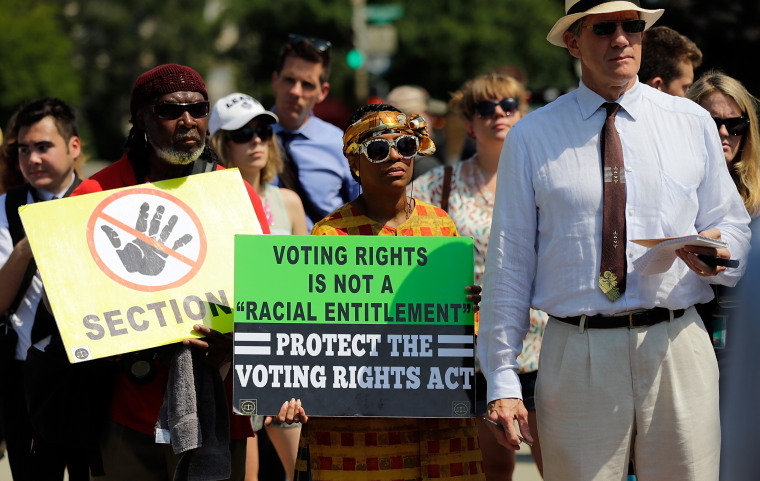 Supporters of the Voting Rights Act listen to speakers discussing today's rulings outside the U.S. Supreme Court building on June 25, 2013 in Washington, DC. (Photo by Win McNamee/Getty Images)