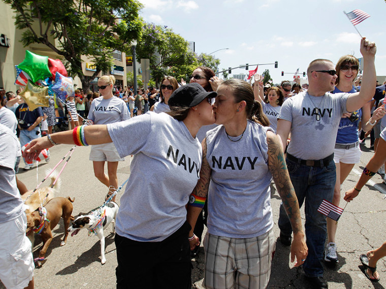 In this July 16,2011 photo, two women, both active duty sailors in the Navy who gave their names as Nikki, left, and Lisa, kiss as they march in the Gay Pride Parade in San Diego. (Photo by Gregory Bull/AP)