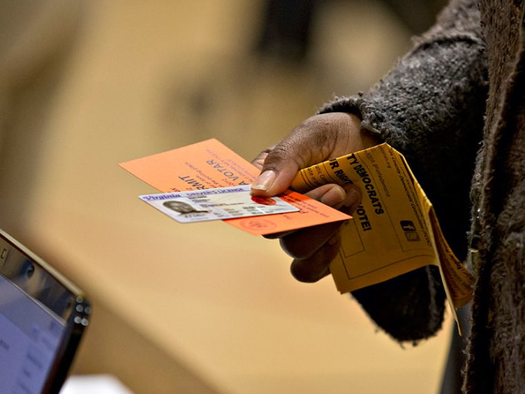 In this Nov. 6, 2012 file photo, a voter holds their voting permit and ID card at the Washington Mill Elementary School near Mount Vernon, Va. Across the South, Republicans are working to take advantage of a new political landscape after a divided U.S....