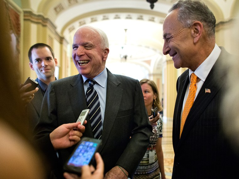 Republican Senator from Arizona John McCain (L) and Democratic Senator from New York Chuck Schumer (R) talk with the media outside the Senate chamber after the immigration bill passed a crucial vote to move forward to a final vote in the US Capitol in...