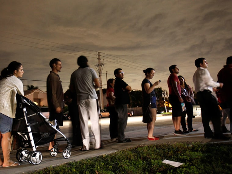 This Nov. 6, 2012 file photo shows voters lined up in the dark to beat the 7 p.m. deadline to cast their ballots at a polling station in Miami. (Photo by Wilfredo Lee/AP)
