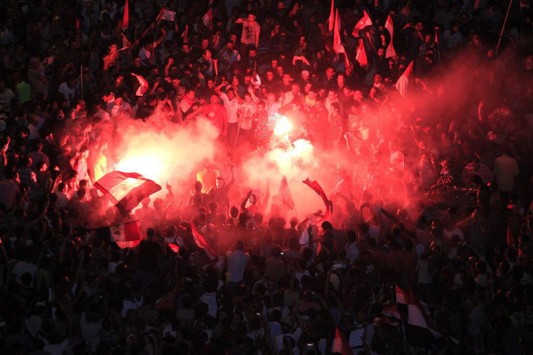 Protesters opposing Egyptian President Mohamed Morsi gather near a lit a flare during a protest at Tahrir Square in Cairo June 30, 2013. Egyptians poured onto the streets on Sunday, swelling crowds that opposition leaders hope will number into the...