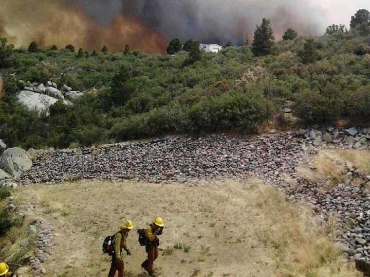 Firefighters move away from the Yarnell Hill Fire, near the town of Yarnell, Ariz., about 80 miles from Phoenix in this June 30, 2013, handout photo. Nineteen firefighters were killed battling a fast-moving wildfire. (Arizona State Forestry Division...