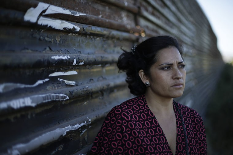 In a June 23, 2012 photo, Mauricia Horta Fuentes, 36, at the fence marking the US-Mexico border in Tijuana, Mexico.  (Photo by Gregory Bull/AP)