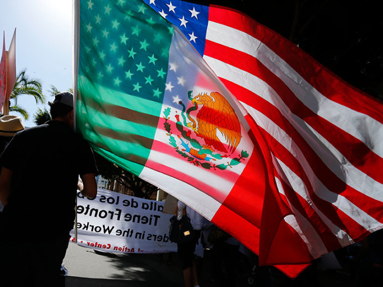 A youth carries national flags of the U.S. and Mexico through the streets of San Diego, during a May Day demonstration and march in California May 1, 2013.  (Photo by Mike Blake/Reuters)