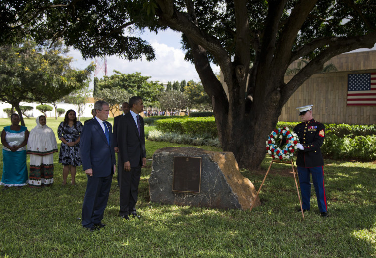 U.S. President Barack Obama and former U.S. president George W. Bush as a Marine places a wreath to honor the victims of the U.S. embassy bombing on Tuesday, July 2, 2013, in Dar Es Salaam, Tanzania. The president is traveling in Tanzania on the final...