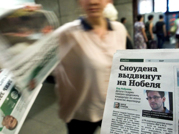 "An employee distributes newspapers, with a photograph (R) of former U.S. spy agency contractor Edward Snowden seen on a page, at an underground walkway in central Moscow July 2, 2013. The headline reads: ""Snowden will be nominated for Nobel"". (Photo by..."
