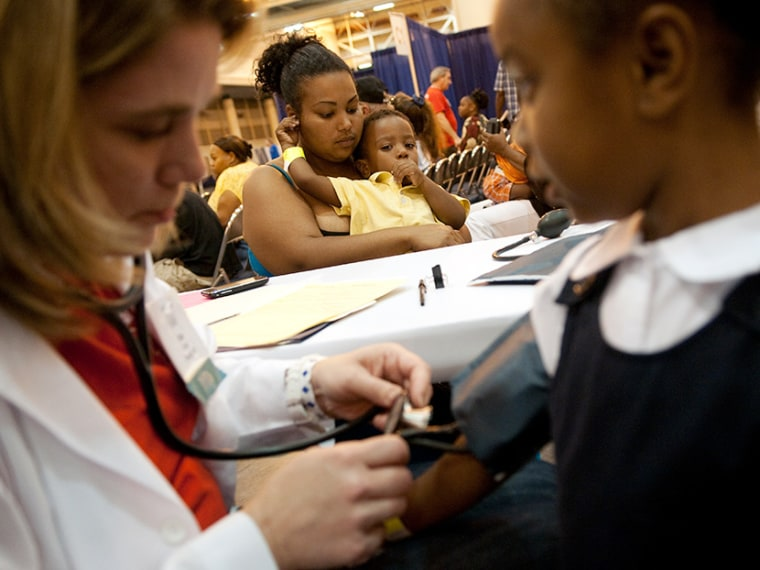 Avanna Parent of New Orleans, LA, holds her two year-old son Leo as Dr. Kim Davis (L) takes a blood pressure test on her five year-old daughter Paige (R) at the New Orleans Communities Are Responding Everyday (C.A.R.E.) Clinic, at the Ernest N. Morial...