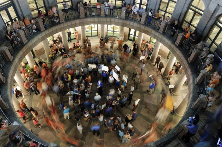 Opponents of an abortion bill walk in circles around supporters of the bill as a committee holds hearings on the bill near by at the Texas state capitol, Tuesday, July 2, 2013, in Austin, Texas. (AP Photo/Eric Gay)