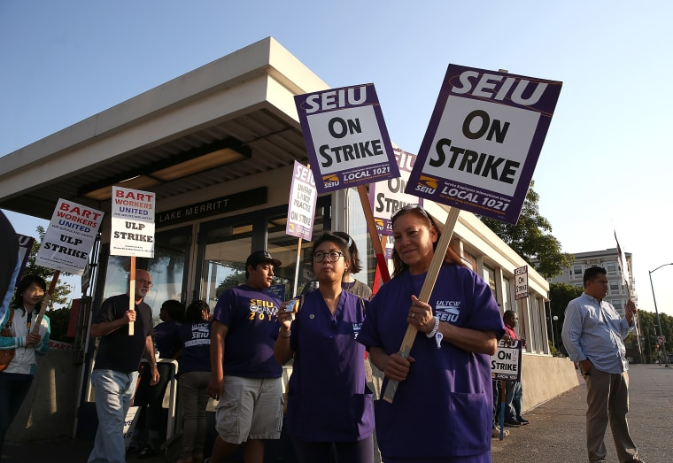 Bay Area Rapid Transit (BART) union workers with SEIU Local 1021 hold signs as they picket in front of the Lake Merritt station on July 2, 2013 in Oakland, California. (Photo by Justin Sullivan/Getty Images)