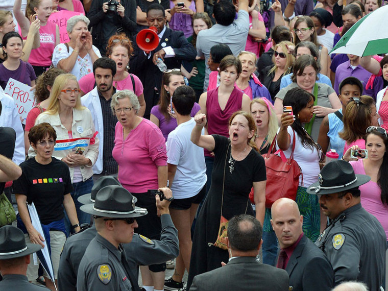 A crowd shouts ''Shame, shame, shame!'' as law enforcement officers stand outside the legislative building after the North Carolina state Senate gave its approval to a series of abortion restrictions Wednesday, July 3, 2013 in Raleigh, North Carolina. ...