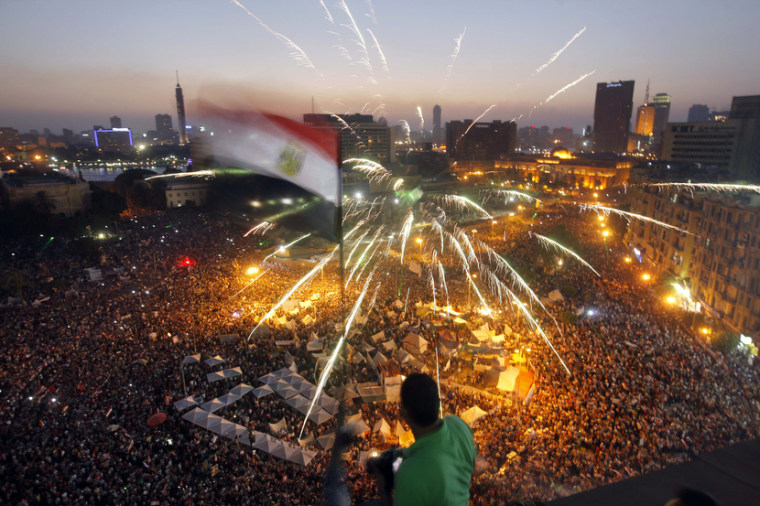 An Egyptian protester waves a national flag as Egyptians gather in Tahrir Square during a demonstration against President Mohammed Morsi in Cairo, Sunday, June 30, 2013. Hundreds of thousands of opponents of Egypt's Islamist president poured out onto...