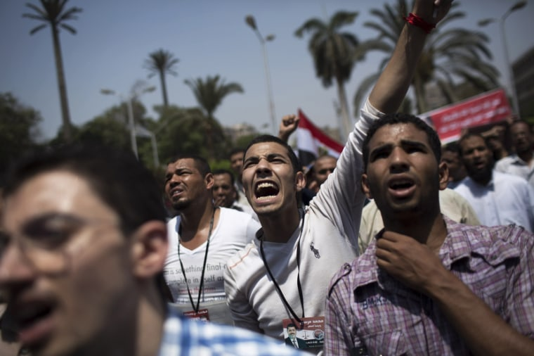 Supporters of Egypt's ousted President Mohamed Morsi chant slogans against the military near Cairo University, where protesters have installed their camp in Giza, southwest of Cairo, Egypt, Monday, July 8, 2013. (Photo by Manu Brabo/AP)