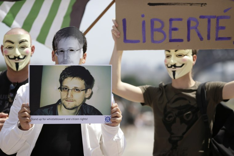 A demonstrator holds up a picture of the former technical contractor of the US Central Intelligence Agency Edward Snowden during a demonstration in support of Snowden at the Place du Trocadero in front of the Eiffel tower in Paris on July 7, 2013. ...