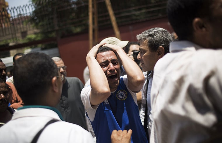 An Egyptian man cries outside a morgue after carrying the corpse of his brother killed near the Republican Guard building in Cairo, Egypt, Monday, July 8, 2013. (Photo by Manu Brabo/AP)