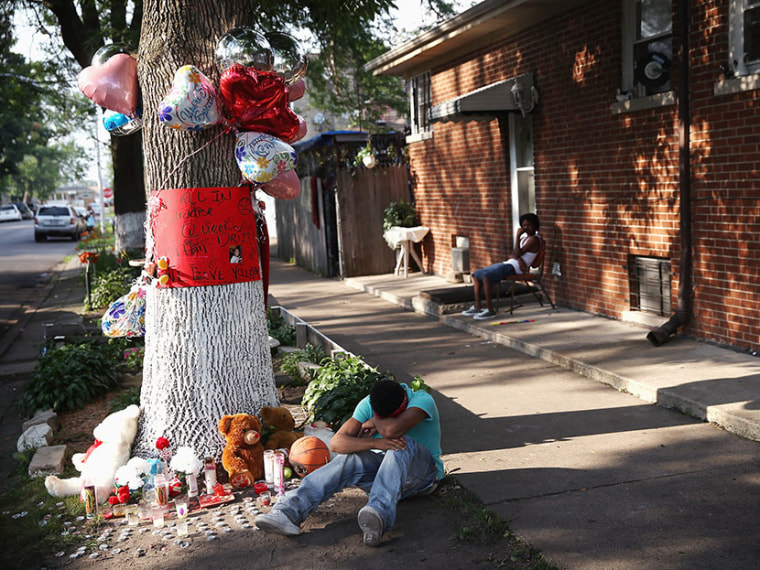 A teenage boy grieves next to a makeshift memorial at the site where Ashley Hardmon was shot and killed on July 4, 2013 in Chicago, Illinois. Hardmon, 19, was killed after being struck in the head by a bullet when two men opened fire on her and a group...