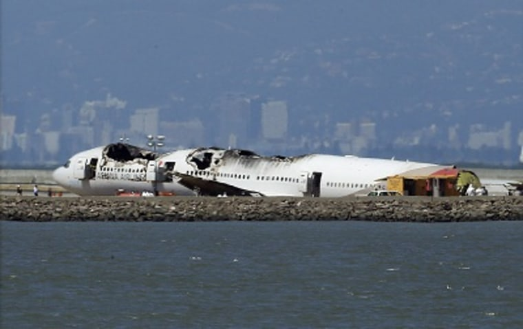 The wreckage of Asiana Airlines Flight 214 that crashed upon landing Saturday at San Francisco International Airport sits on the tarmac Monday, July 8, 2013 in San Francisco. (Photo by Jeff Chiu/AP)