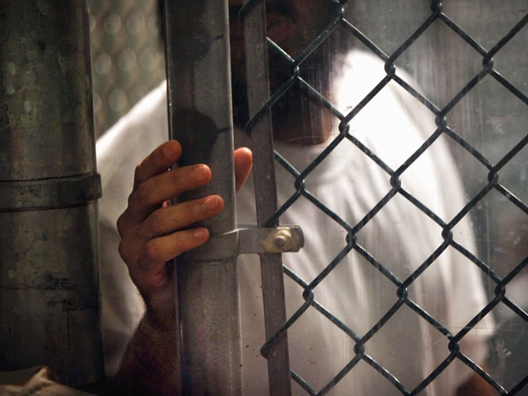 """A detainee stands at a fence inside the detention center for \""""enemy combatants\"""" on September 15, 2010 in Guantanamo Bay, Cuba. (Photo by John Moore/Getty Images)"""