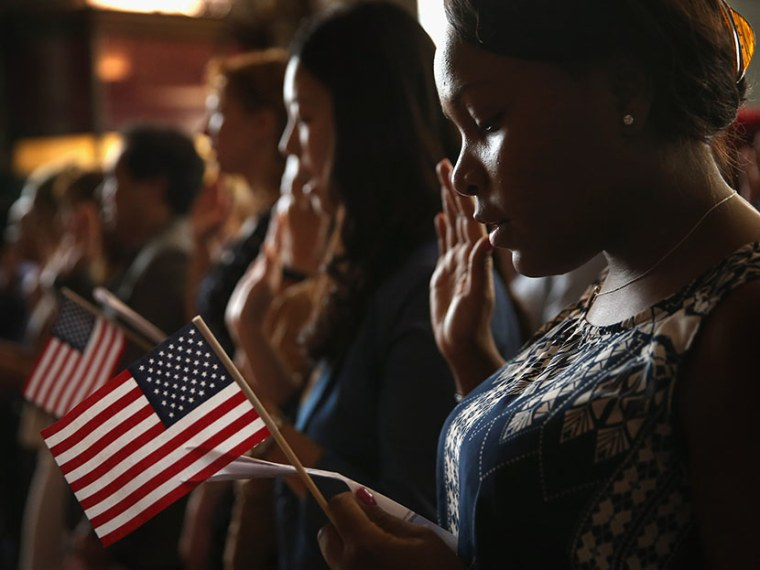 Vishaun Lawrence of Jamaica takes an oath of citizenship during a naturalization ceremony at the Chicago Cultural Center on July 3, 2013 in Chicago, Illinois.  (Photo by Scott Olson/Getty Images)