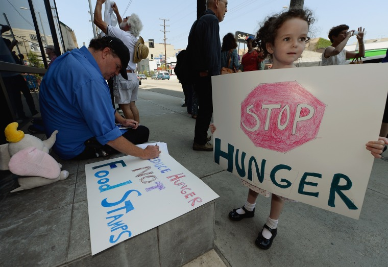 Gracie Shannon-Sanborn, 5, holds a sign as she joins her father Allen Sanborn (L) and members of Progressive Democrats of America and other activists as they hold a rally in front of Rep. Henry Waxman's office on June 17, 2013 in Los Angeles,...