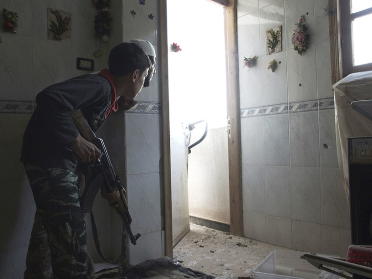 Dany, a 14-year-old fighter, whom activists say is the youngest fighter in the Khadraa brigade operating under the Free Syrian Army, takes position inside a house in Deir al-Zor July 9, 2013.  (Photo by Khalil Ashawi/AP)