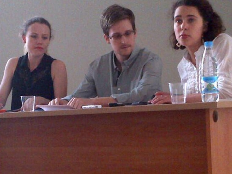 Former intelligence agency contractor Edward Snowden (C) and Sarah Harrison (L) of WikiLeaks speak to human rights representatives in Moscow's Sheremetyevo airport July 12, 2013. The person at right is unidentified.   (Photo by Human Rights Watch...