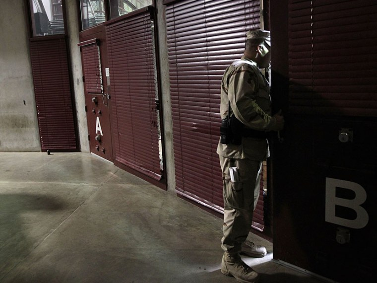 A U.S. military guard checks on detainees in a cell block at Camp 6 in the Guantanamo Bay detention center on March 30, 2010 in Guantanamo Bay, Cuba.  (Photo by John Moore/Getty Images)