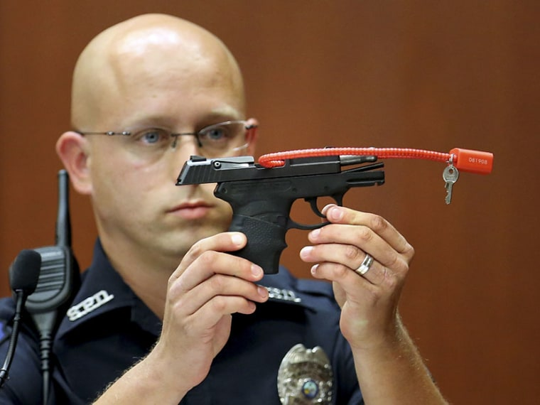 Sanford police officer Timothy Smith holds up the gun that was used to  kill Trayvon Martin, while testifying during George Zimmerman's murder trial in Seminole circuit court in Sanford, Florida, June 28, 2013. (Photo by Joe Burbank/Reuters)