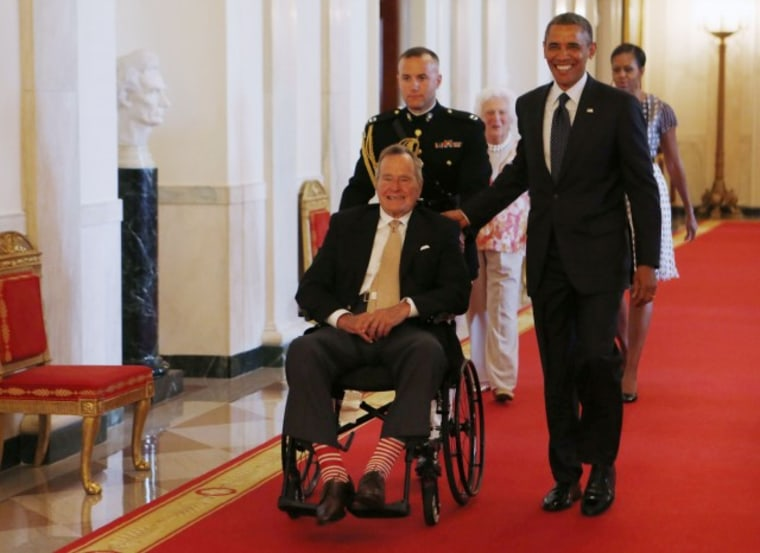 """Former U.S. President George H.W. Bush sits in a wheelchair as he is escorted next to U.S. President Barack Obama (R) as they attend an event honoring the 5,000th winner of the """"Daily Point of Light"""" award in the East Room of the White House in..."""