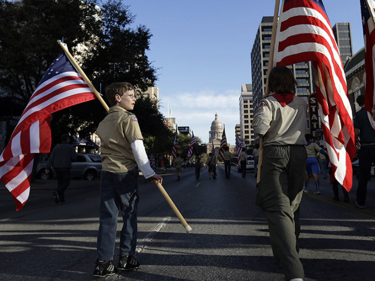 Boy Scouts carry U.S. flags up Congress Avenue towards the Texas Capitol during the annual Boy Scouts Parade and Report to State, Saturday, Feb. 2, 2013, in Austin, Texas. (Photo Eric Gay/AP)