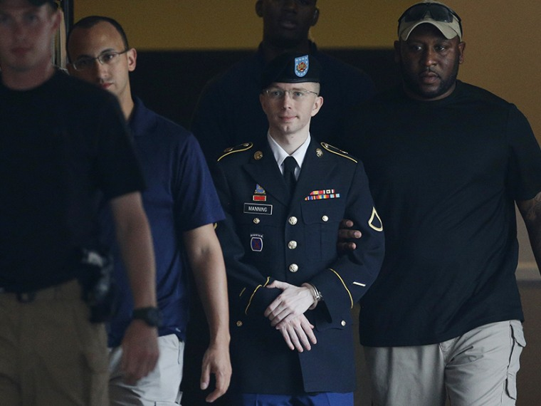 Army Pfc. Bradley Manning, second from right, is escorted to a waiting security vehicle outside of a courthouse in Fort Meade, Md., Monday, July 15, 2013, after appearing for a hearing at his court martial. (Photo by Patrick Semansky/AP)