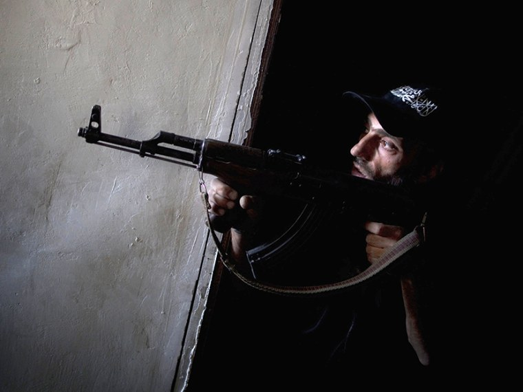 A rebel fighter points his gun towards pro-government forces' positions during clashes in the Salaheddine district of the northern Syrian city of Aleppo, on July 9, 2013.  (Photo by JM Lopez/AFP/Getty Images)