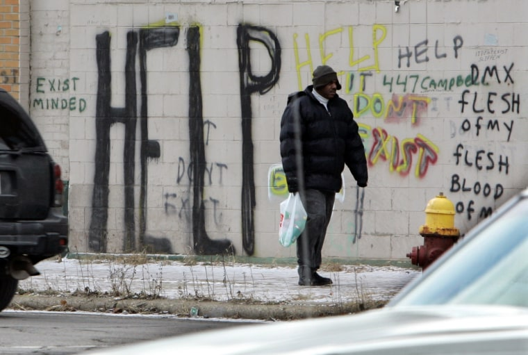 FILE - A pedestrian walks by graffiti in downtown Detroit in a Dec. 12, 2008, file photo. Detroit became the largest city in U.S. history to file for bankruptcy on Thursday, July 18, 2013, when state-appointed emergency manager Kevyn Orr asked a...