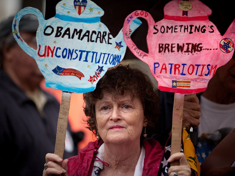 """Carlene Cahill of Petersburg, Va., holds up a set of signs she made during a Tea Party Patriots' """"Road To Repeal Rally"""" on a rainy day March 24, 2012,  in Washington, DC.  (Photo by Allison Shelley/Getty Images)"""