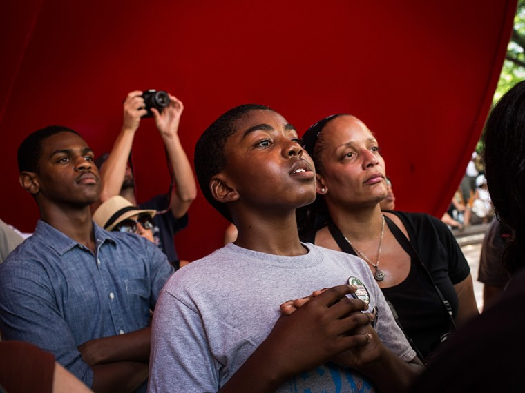 A boy cranes his head to hear a speaker while attending a rally in support of Trayvon Martin, organized by the Reverand Al Sharpton, in response to the non-guilty verdict for George Zimmerman on July 20, 2013 in New York City.  (Photo by Andrew Burton...