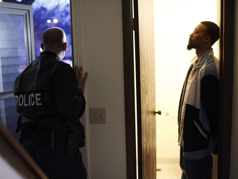 Suspect Gerald Ware (R) stands handcuffed in the doorway of his home as police conduct a raid in search of illegal drugs during the execution of a search warrant for marijuana in Kalamazoo, Michigan, on November 12, 2009 file picture.  (Photo by John...