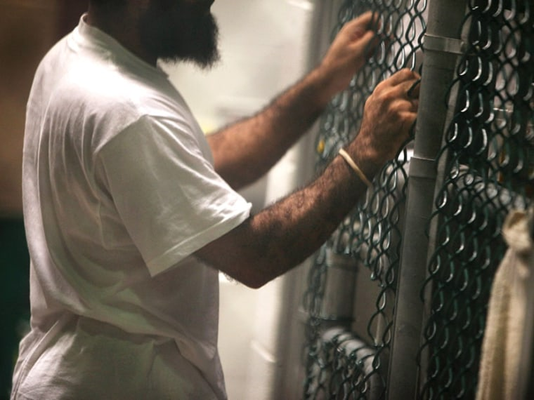 """A detainee speaks through a fence at the U.S. detention center for """"enemy combatants"""" on September 15, 2010 in Guantanamo Bay, Cuba.  (Photo by John Moore/Getty Images)"""