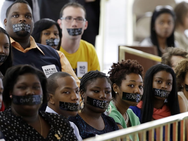 Members of North Carolina student chapters of the NAACP  and opponents of voter ID legislation wear tape over their mouths while sitting silently in the gallery of the House chamber of the North Carolina General Assembly where lawmakers debated and...