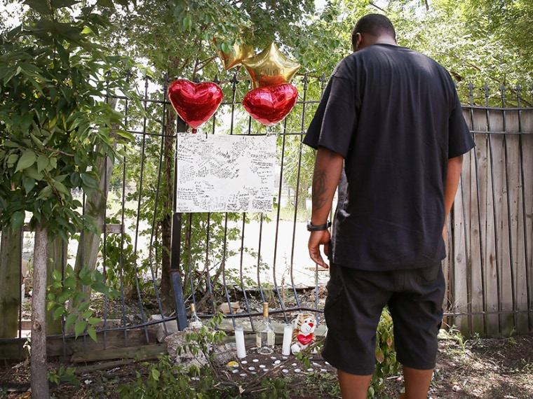 Anthony (no last name available) looks over a memorial for his friend Eugene Clark, 25, who was shot and killed Saturday on July 22, 2013 in Chicago, Illinois.  (Photo by Scott Olson/Getty Images)