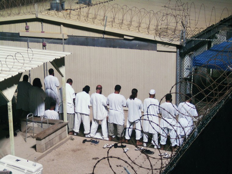 Detainees participate in an early morning prayer session at Camp IV at the detention facility in Guantanamo Bay U.S. Naval Base August 5, 2009. (Photo by Deborah Gembara/Reuters)