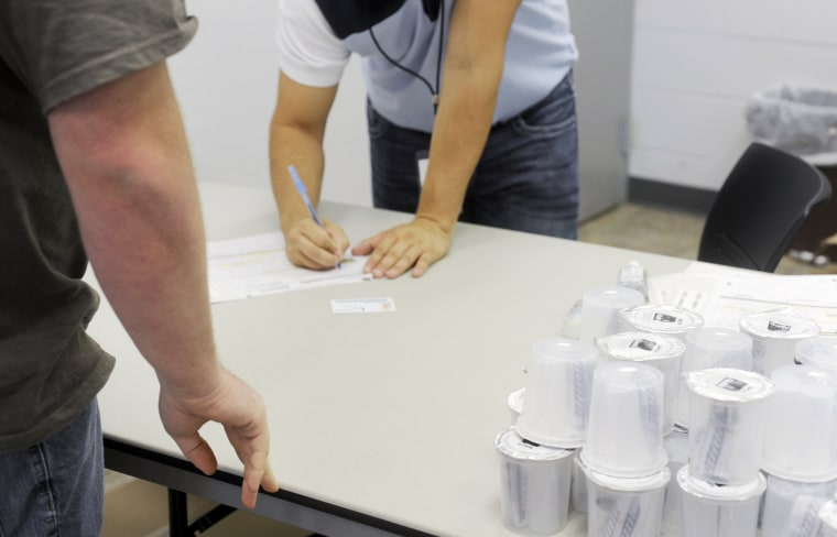 Caleb Stoll, of Springfield, Mo.,with Employee Screening Services,  right, completes paperwork as a student waits near the specimen cups for instructions ...
