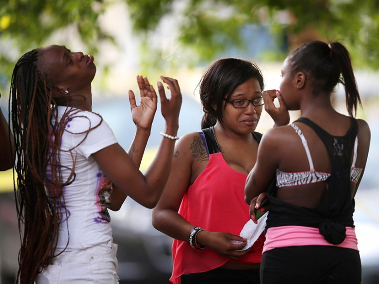 Young women watch as police prepare to remove the remains of their friend after he was shot and killed on June 22, 2013 in Chicago, Illinois. (Photo by Scott Olson/Getty Images)