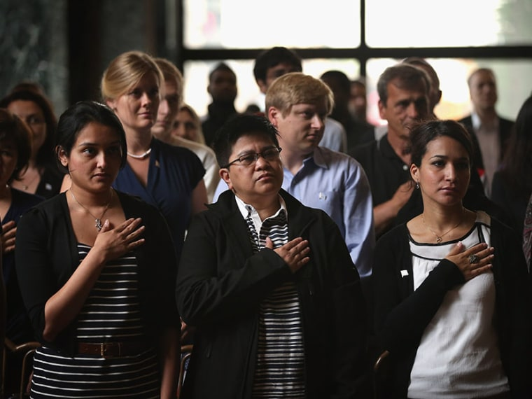 New U.S. citizens recite the Pledge of Allegiance during a naturalization ceremony at the Chicago Cultural Center on July 3, 2013. (Photo by Scott Olson/Getty)
