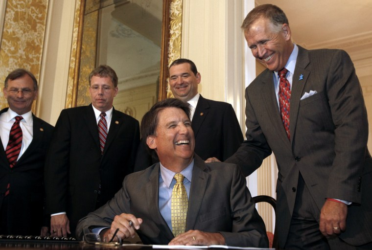 Gov. Pat McCrory, flanked by members of the N.C. General Assembly like Speaker of the House Thom Tillis, right, jokes before he signs the HB 998 for Tax Reform in the ballroom at the Executive Mansion in Raleigh, N.C. on Tuesday, July 23, 2013. (AP...
